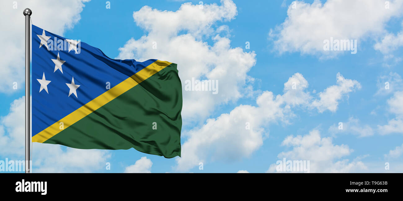 Solomon Islands flag waving in the wind against white cloudy blue sky. Diplomacy concept, international relations. - Stock Image