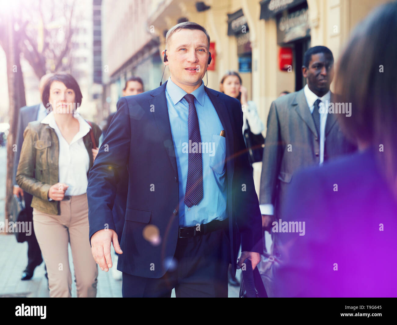 Confident businessman in formal suit walking on city street to office at rush hour - Stock Image
