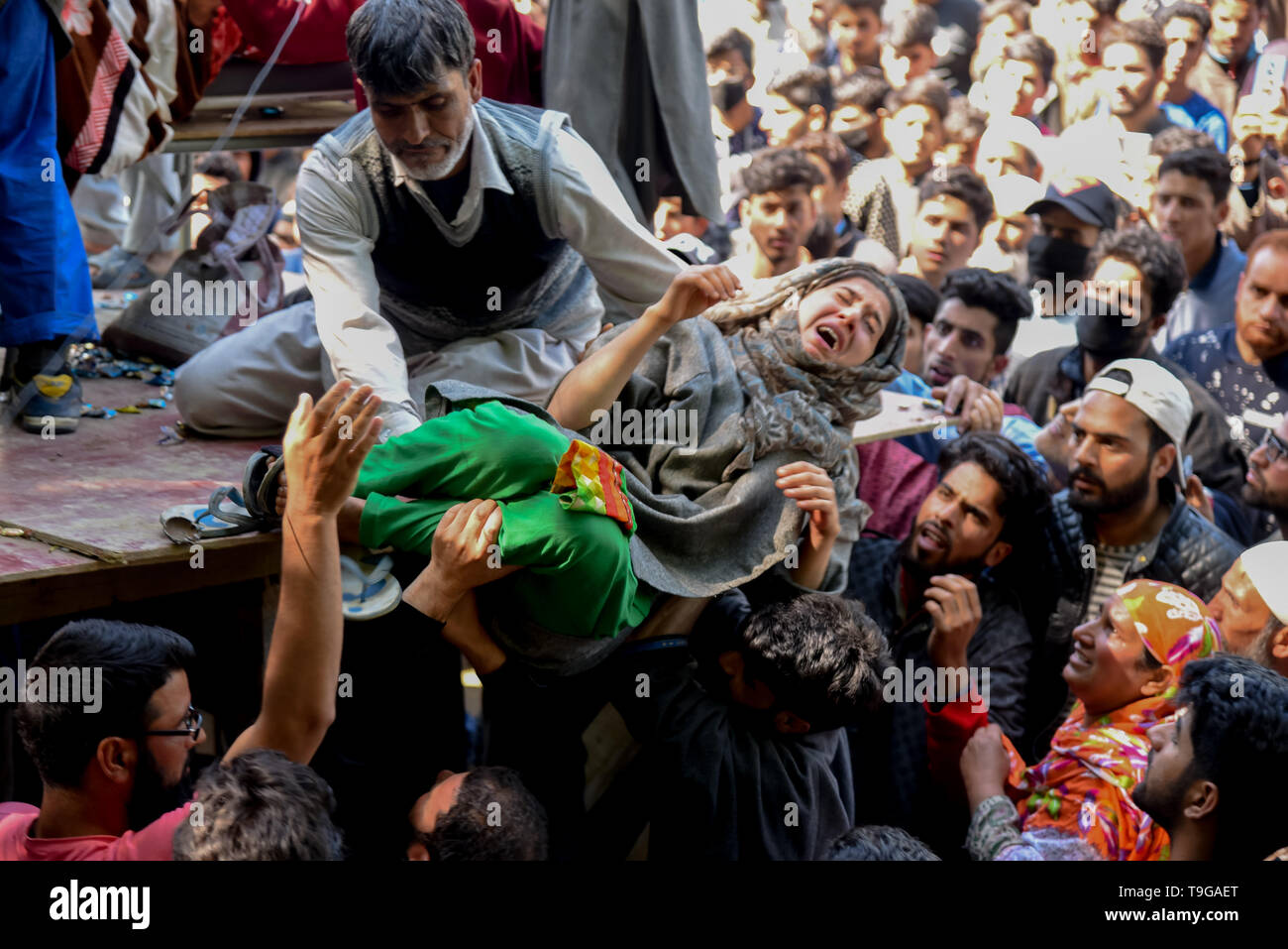 A relative of the slain Kashmiri Rebel Showkat Ahmed seen mourning next to his dead body during the funeral ceremony at his residence in Pulwama, South of Srinagar. Thousands attended the funeral ceremony of slain Showkat Ahmed Dar at his residence in Panzgam Pulwama. Showkat was among the three Kashmiri Rebels killed in a gunfight in Pulwama. - Stock Image