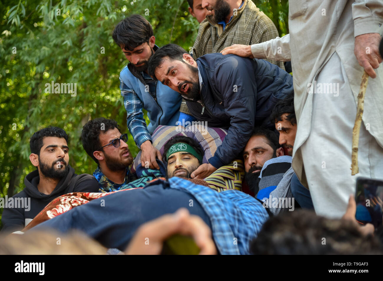 (EDITORS NOTE: Image depicts death) Relatives of Kashmiri Rebel Showkat Ahmed are seen gathered around his dead body during the funeral procession in Pulwama, South of Srinagar. Thousands attended the funeral ceremony of slain Showkat Ahmed Dar at his residence in Panzgam Pulwama. Showkat was among the three Kashmiri Rebels killed in a gunfight in Pulwama. - Stock Image