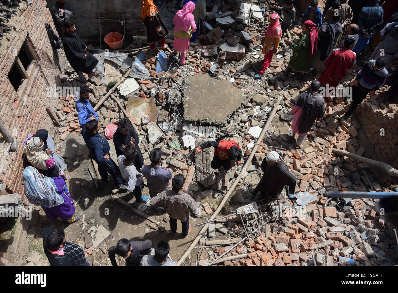 Kashmiri villagers are seen inspecting a damaged house after a gunfight in Pulwama, South of Srinagar. Four Kashmiri Rebels were killed on Saturday in two separate gunfights in Jammu and Kashmir's Pulwama and Baramulla districts. - Stock Image