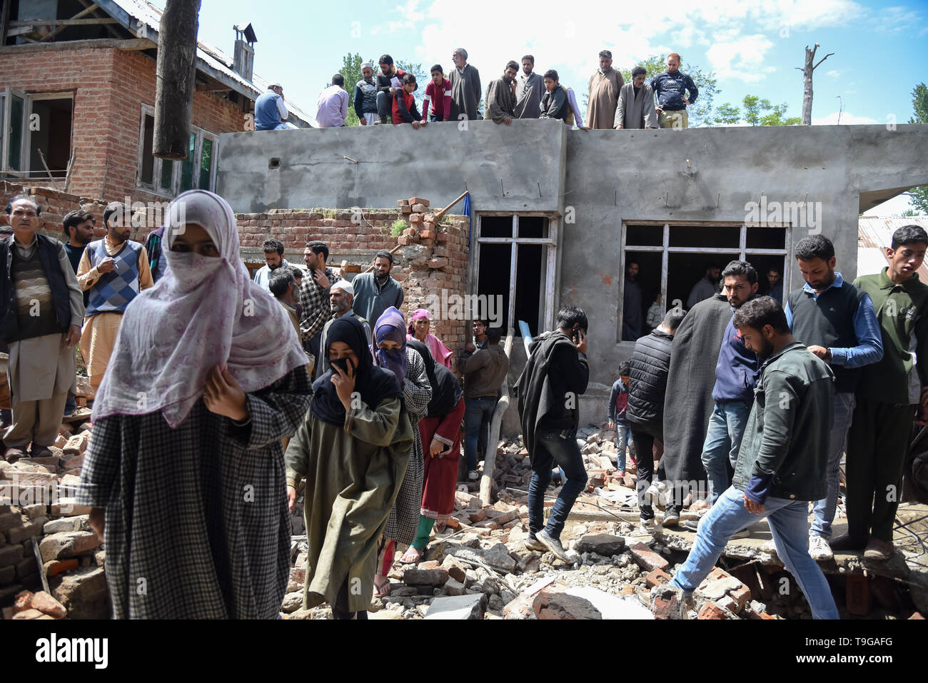 Kashmiri residents are seen entering partially damaged house after a gunfight in Pulwama, South of Srinagar. Four Kashmiri Rebels were killed on Saturday in two separate gunfights in Jammu and Kashmir's Pulwama and Baramulla districts. - Stock Image