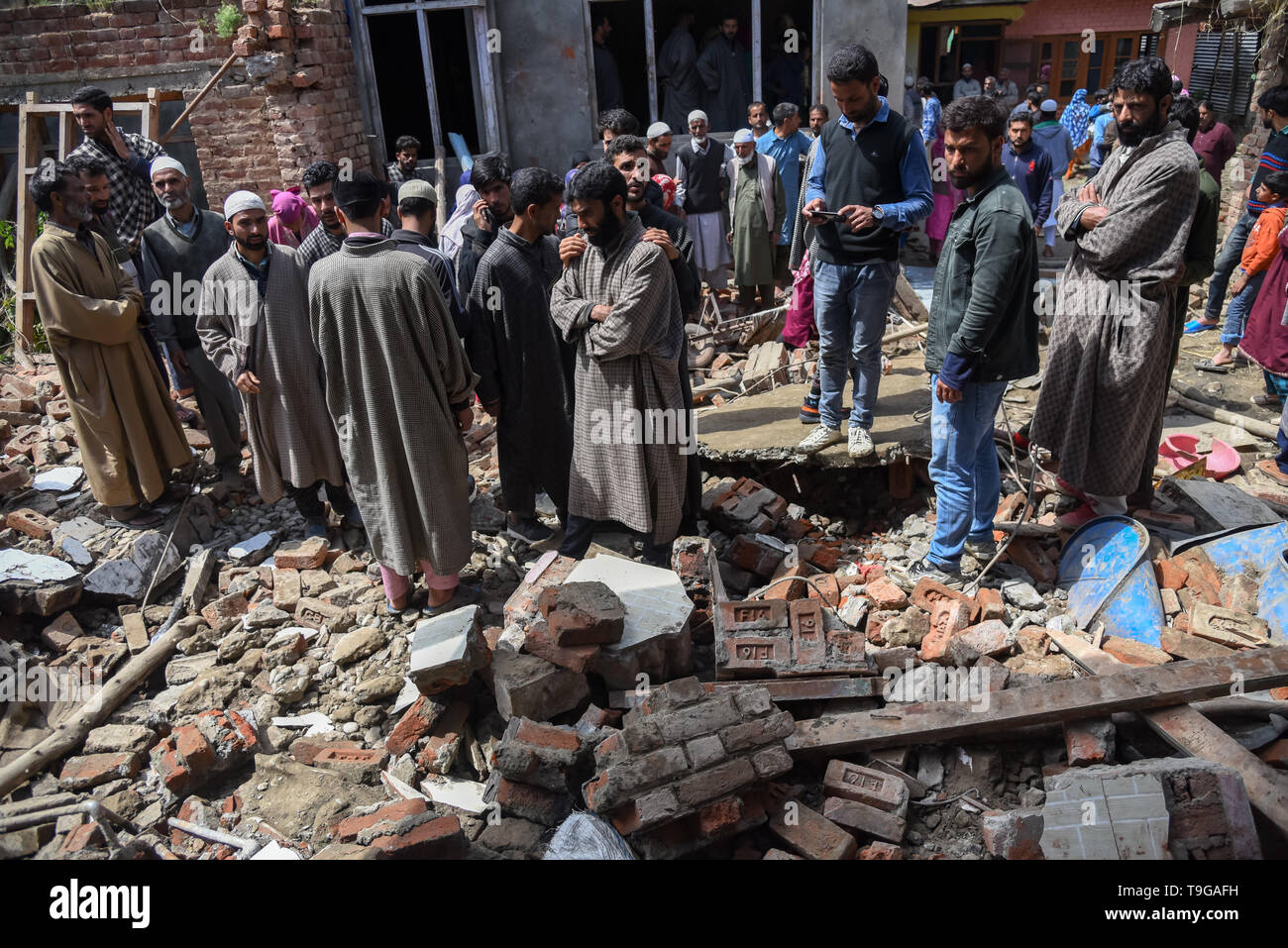 Kashmiri villagers are seen gathered around a partially damaged house after a gunfight in Pulwama, South of Srinagar. Four Kashmiri Rebels were killed on Saturday in two separate gunfights in Jammu and Kashmir's Pulwama and Baramulla districts. - Stock Image