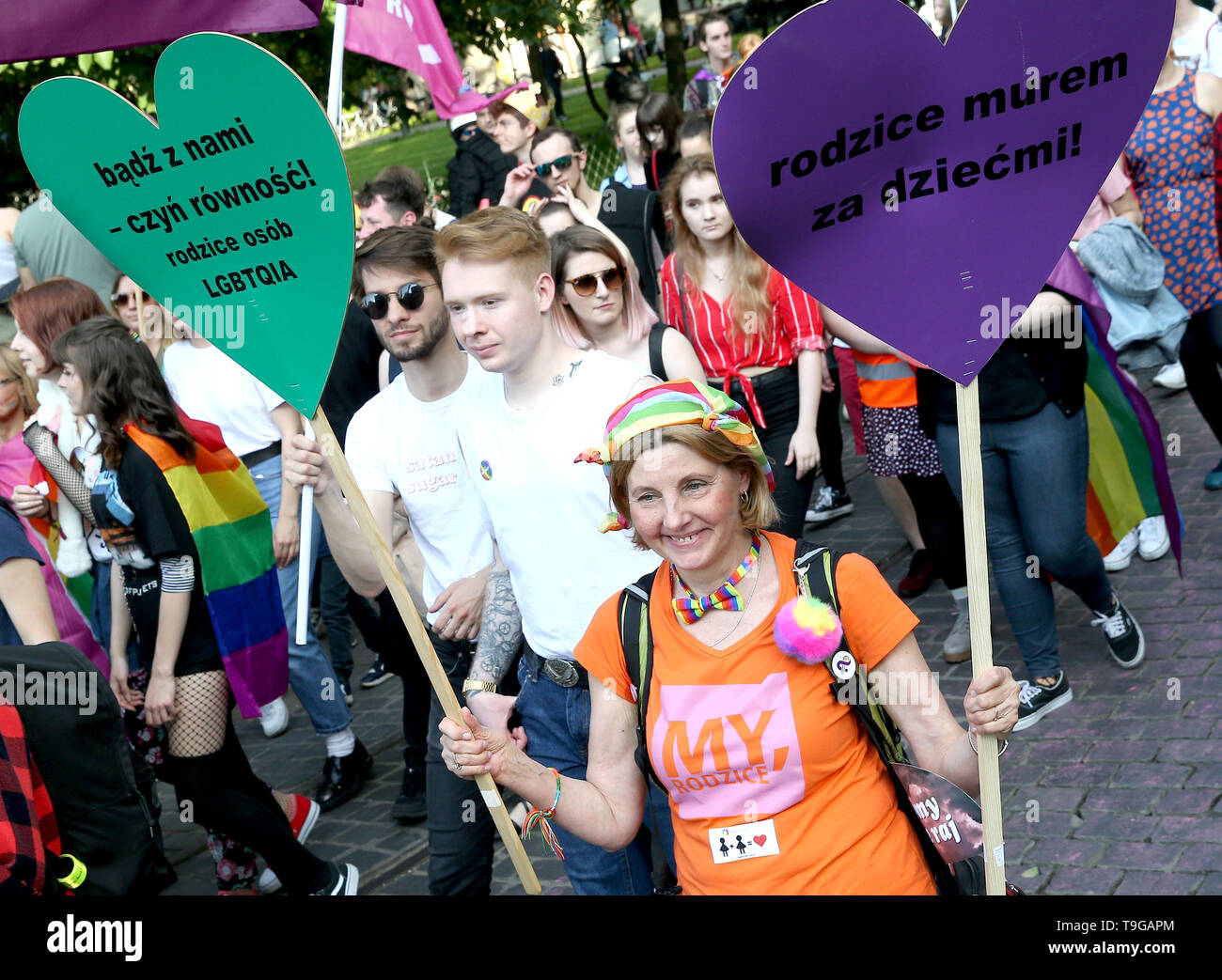 People are seen during the Equality March in Krakow. LGBT people and their supporters walk through the streets of Krakow to celebrate diversity and tolerance and express their opposition to discrimination and exclusion. The march was met in the city center by anti LGBT protesters from the far right organizations. - Stock Image