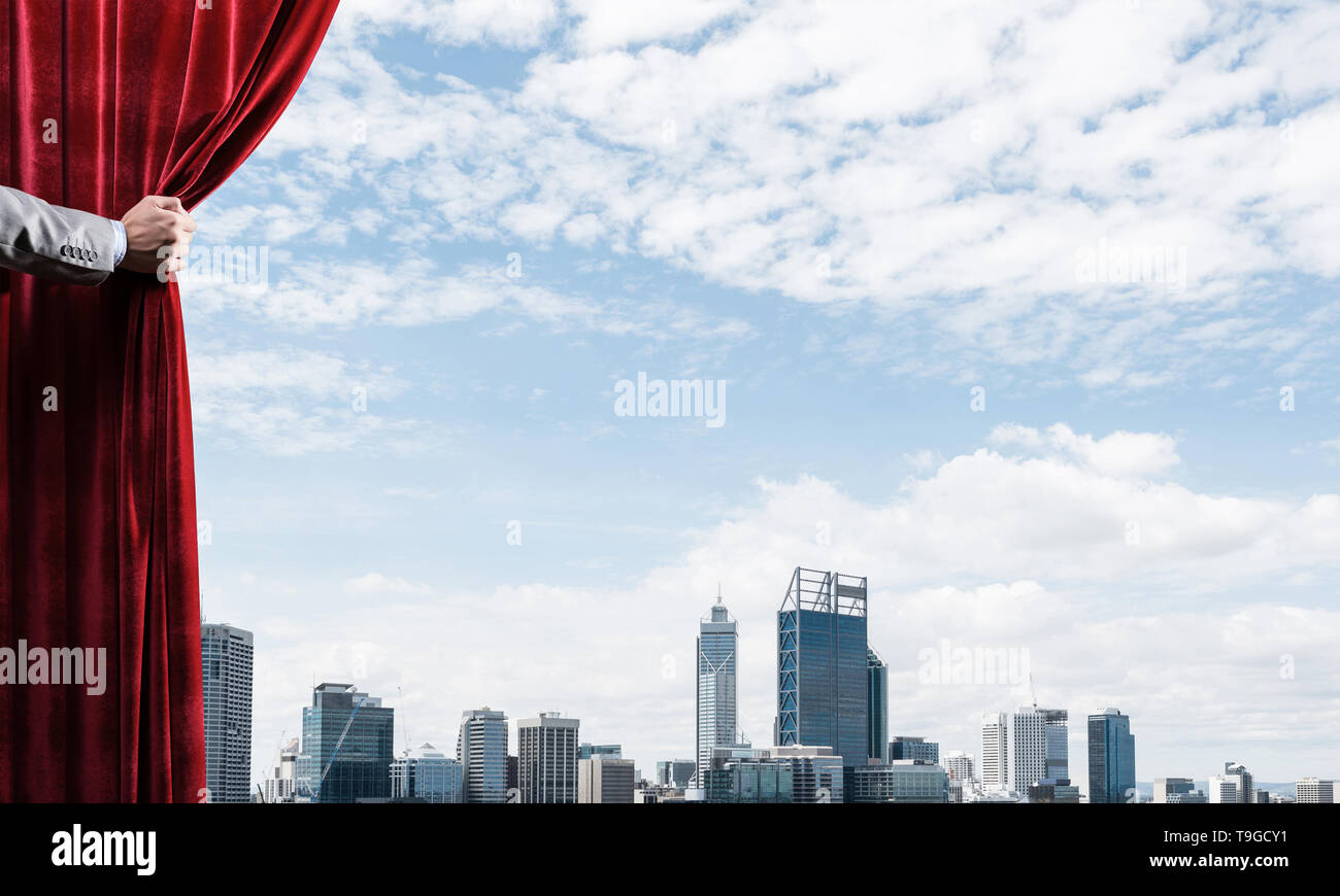 Modern business cityscape behind curtain opened by businessman hand - Stock Image