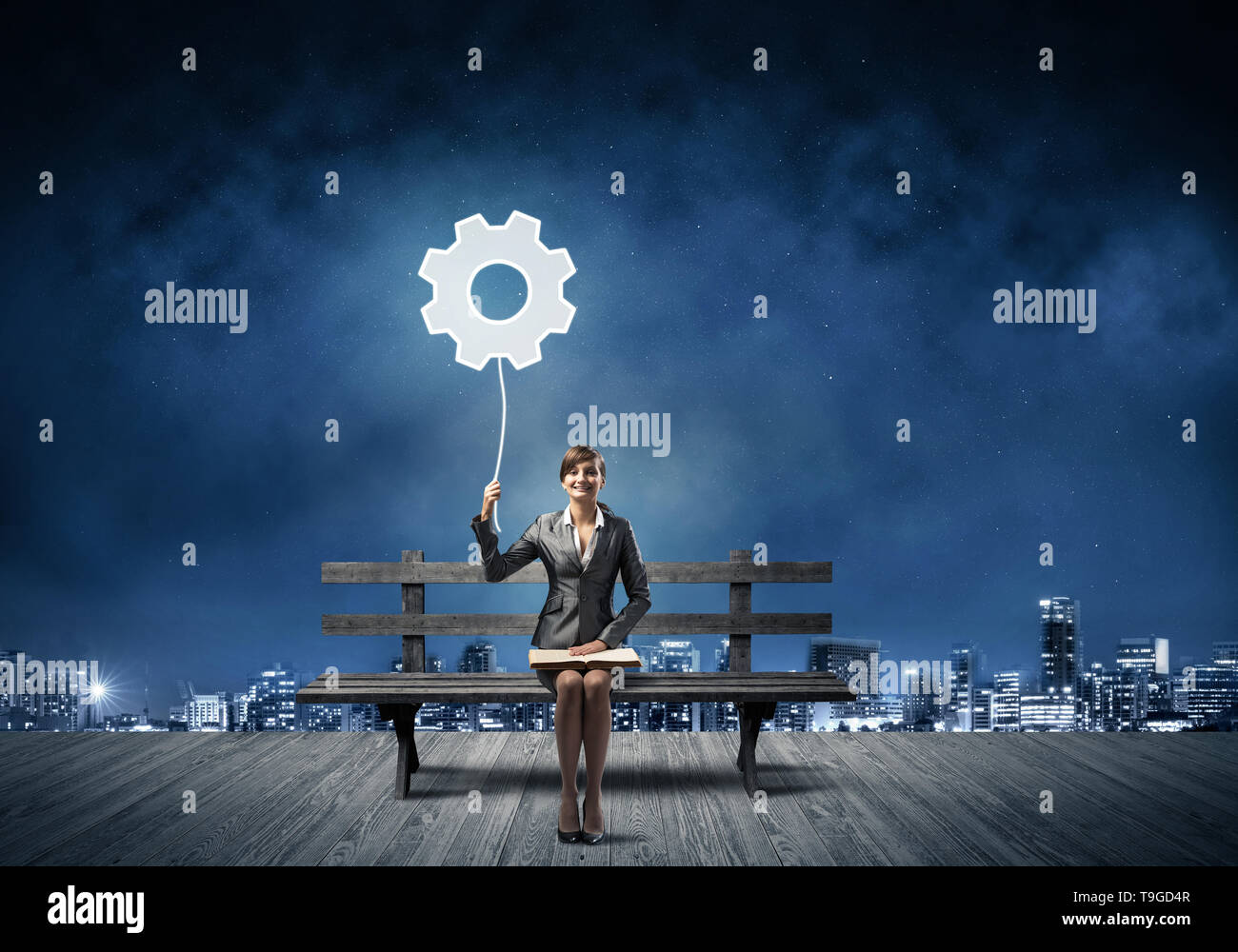 Young woman holding open book on bench - Stock Image