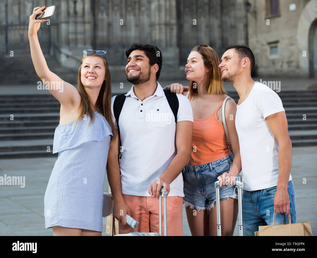 Four happy travellers smiling and making selfie with mobile phone - Stock Image