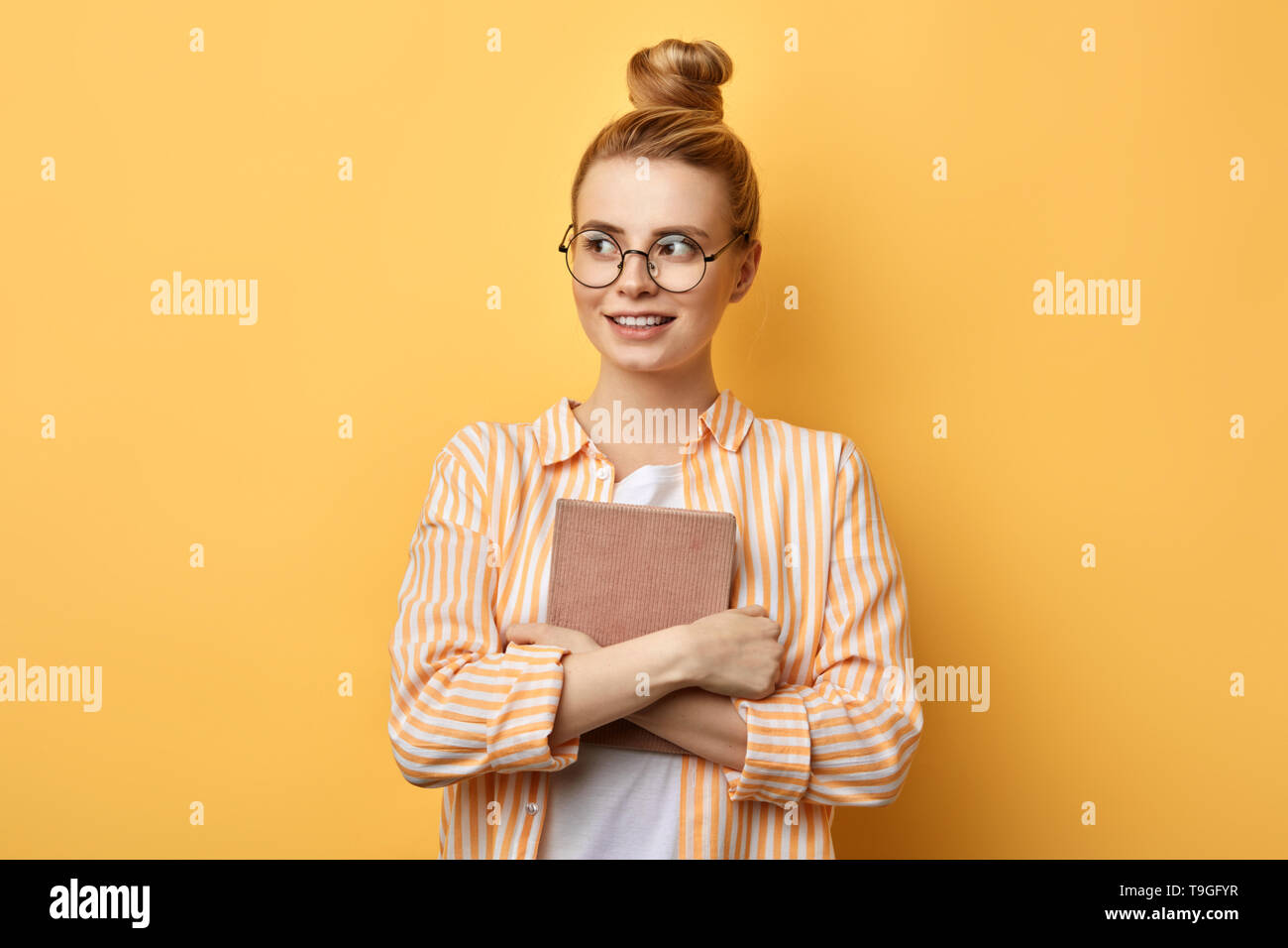 Happy young beautiful woman with hairbun standing and holding tablet over yellow background and looking aside . education concept. copy space - Stock Image