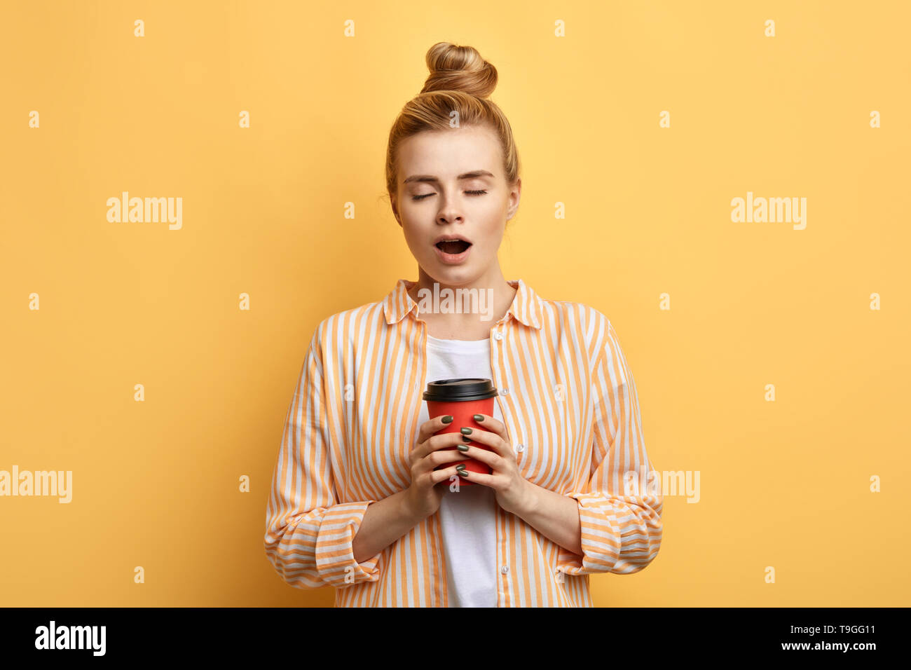 exhausted young blonde woman wants to sleep. attractive woman with closed eyes holding a disposable cup and yawning. isolated yellow background - Stock Image