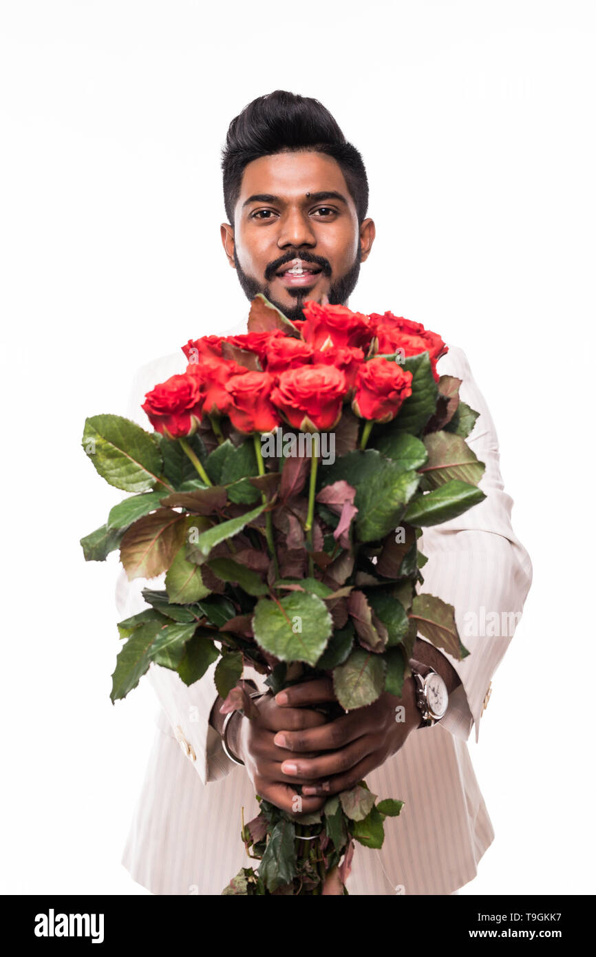 handsome man holding bouquet of red roses, isolated on grey - Stock Image