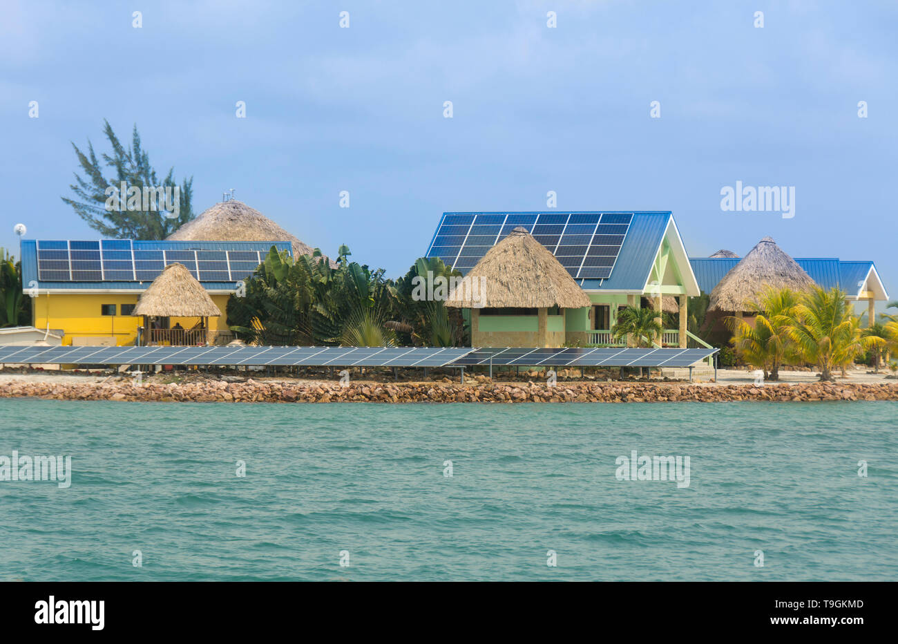 Small island residence with solar panels on rooftops. Near Placencia, Belize - Stock Image