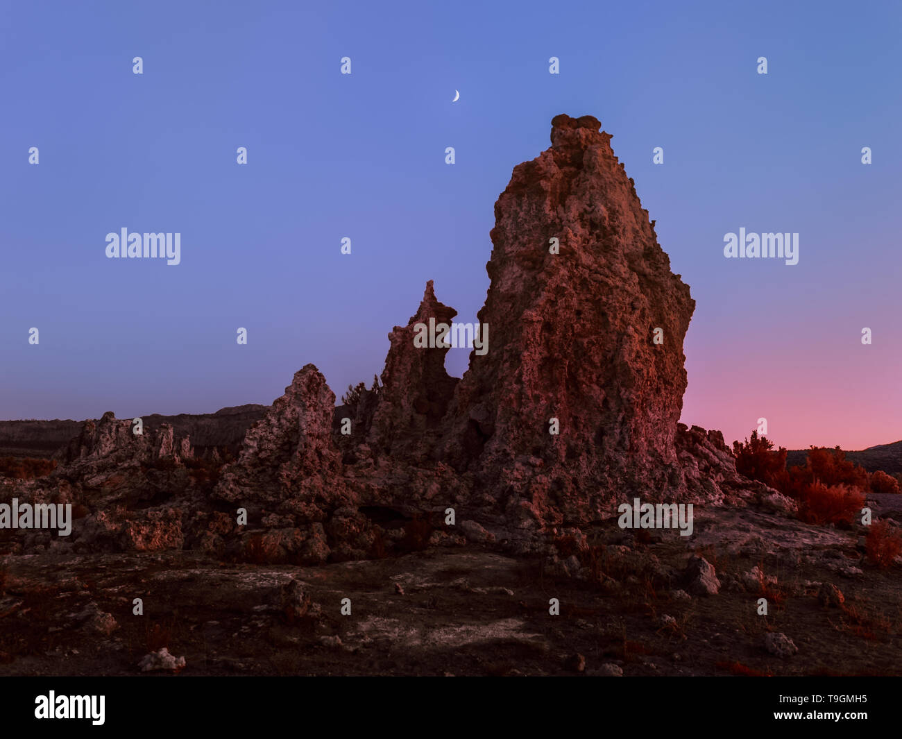 Unearthly scenery with bizarre rock formations and crescent moon - Stock Image