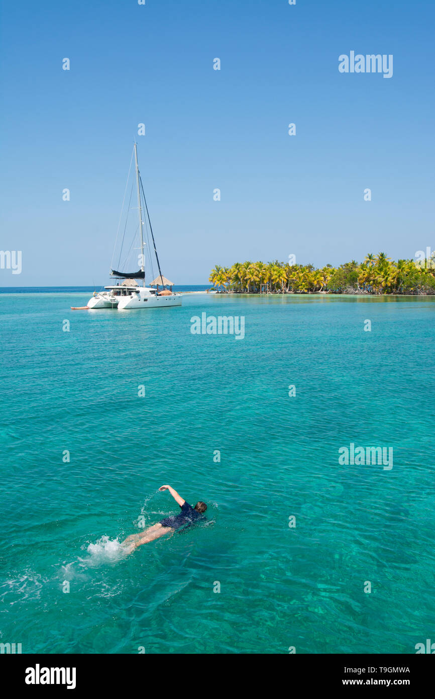 Swimmers and cruising catamaran at North Long Coco Plum Caye, Belize - Stock Image
