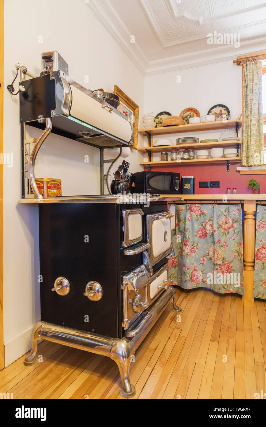 Elmira antique electric cooking stove in kitchen with birch wood floorboards inside an old 1920s house, Quebec, Canada. This image is property released. CUPR0349 - Stock Image