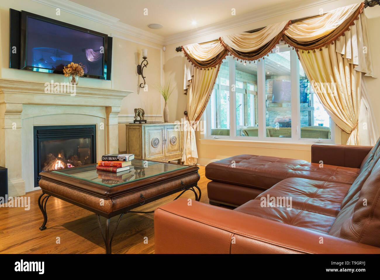 Picture of: Reddish Brown L Shaped Leather Sectional Sofa And Glass Top Coffee Table In Living Room With Gas Fireplace Inside A Luxurious Residential Home Quebec Canada This Image Is Property Released Cupr0353 Stock Photo