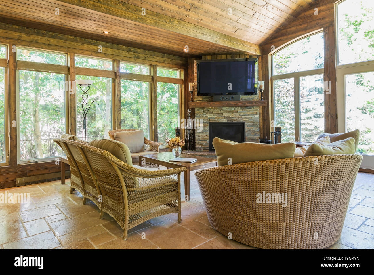 Wicker Chairs And Sofa In Solarium With Tan Marble Tile Floor