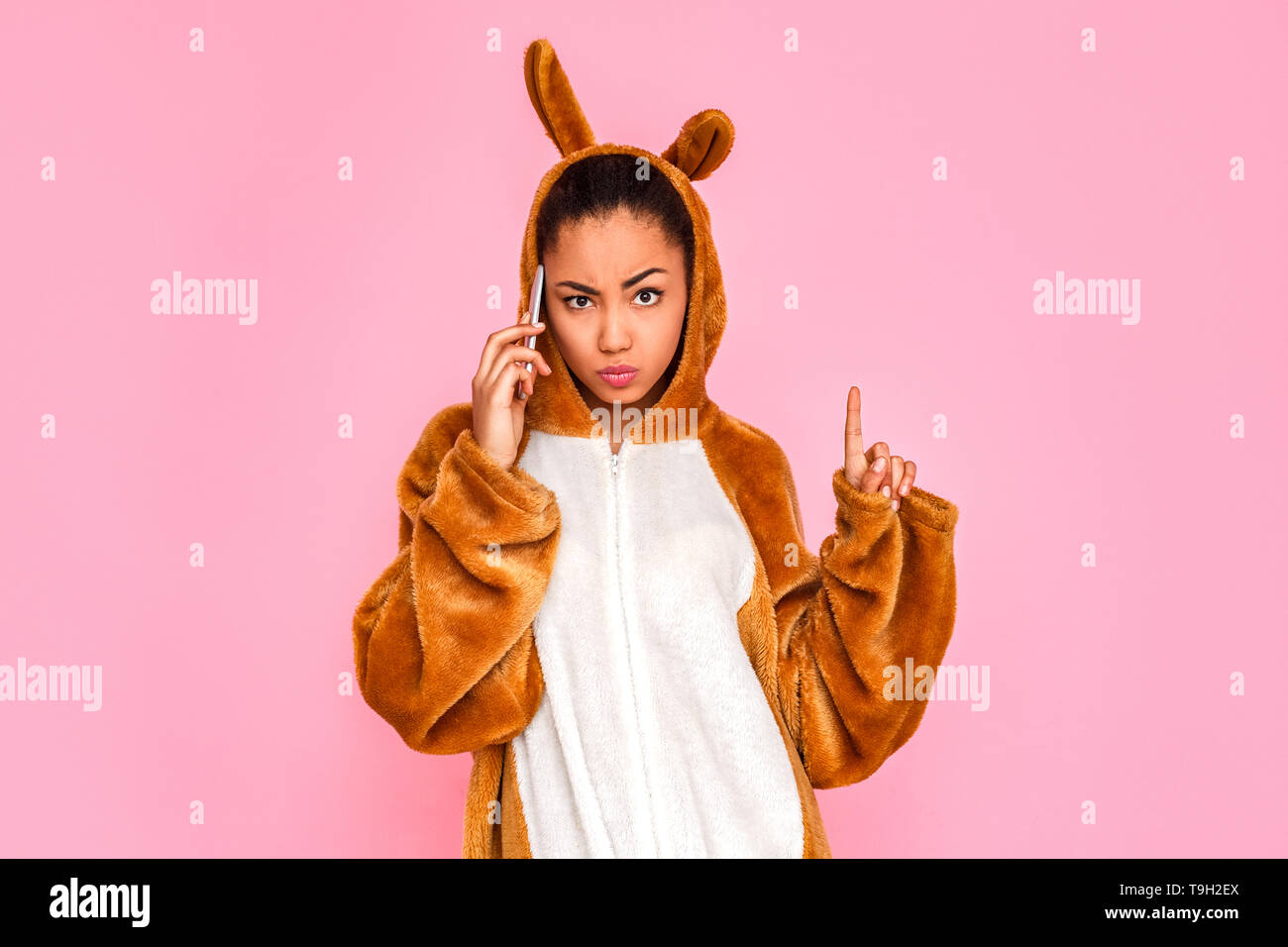 Young woman in bunny kigurumi standing isolated on pink background talking on smartphone with friend looking camera pointing up grimacing cool - Stock Image