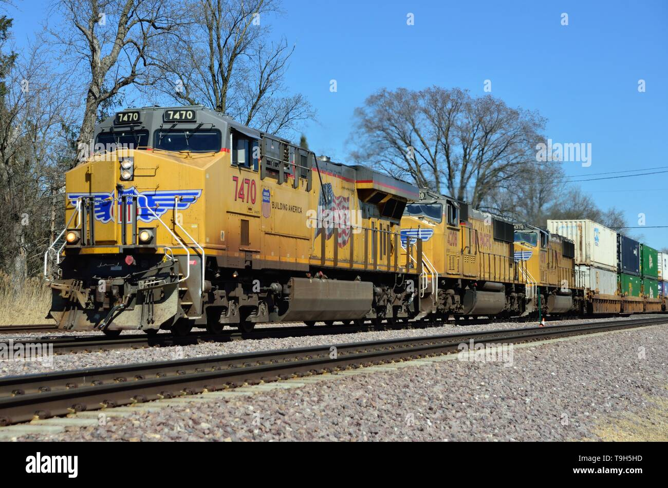 LaFox, Illinois, USA. A trio of Union Pacific Railroad locomotives lead a stack freight westbound through LaFox, Illinois on its way from Chicago. - Stock Image