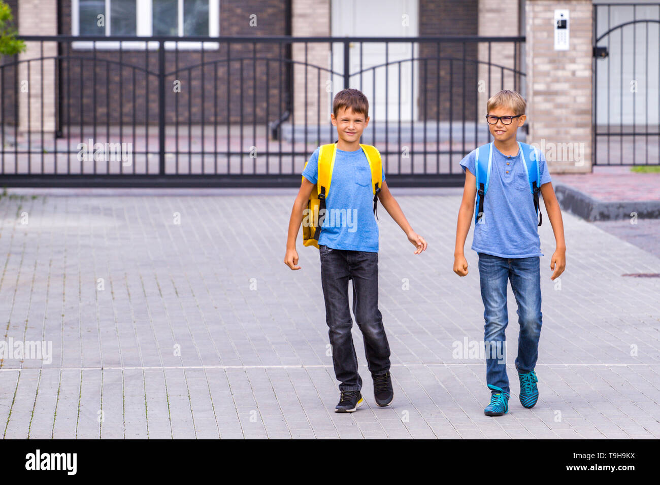 Two happy shoolboys with backpacks go to school in the morning - Stock Image