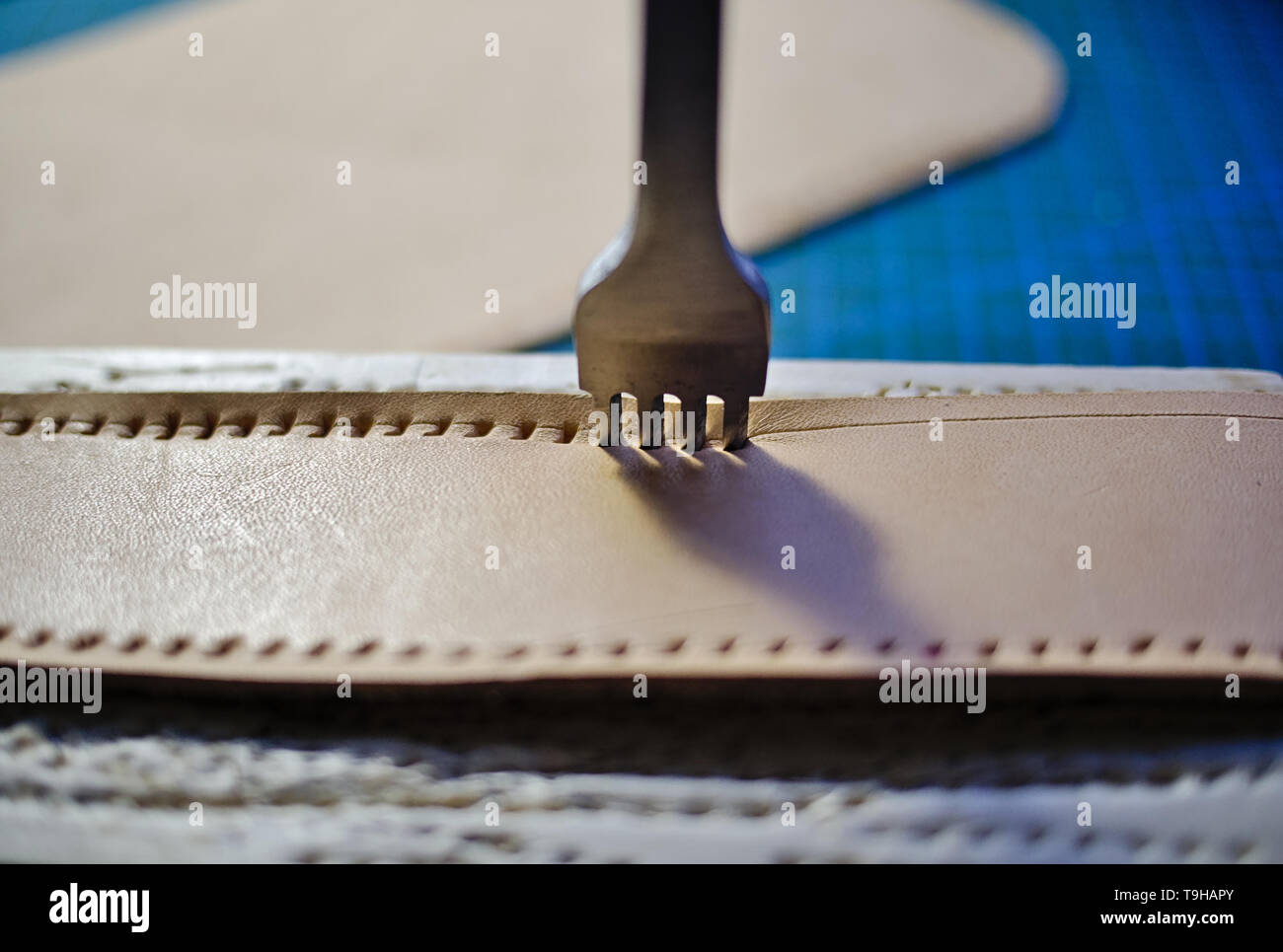 Leather working four prong chisel hole punch close up. Punching holes for stiching with metal tool. Selective focus. - Stock Image