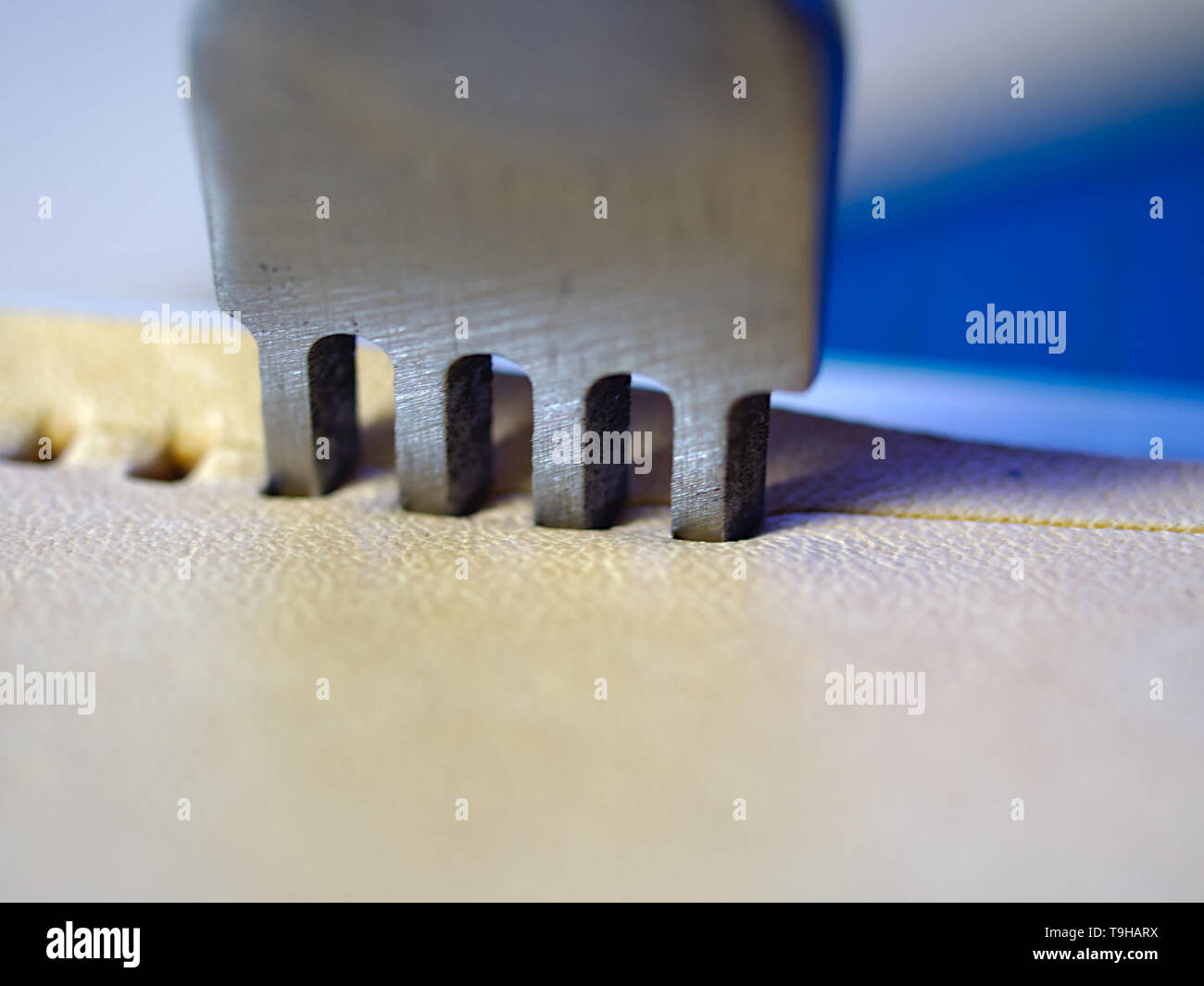 Leather working four prong chisel hole punch close up macro. Punching holes for stiching with metal tool. Selective focus. - Stock Image