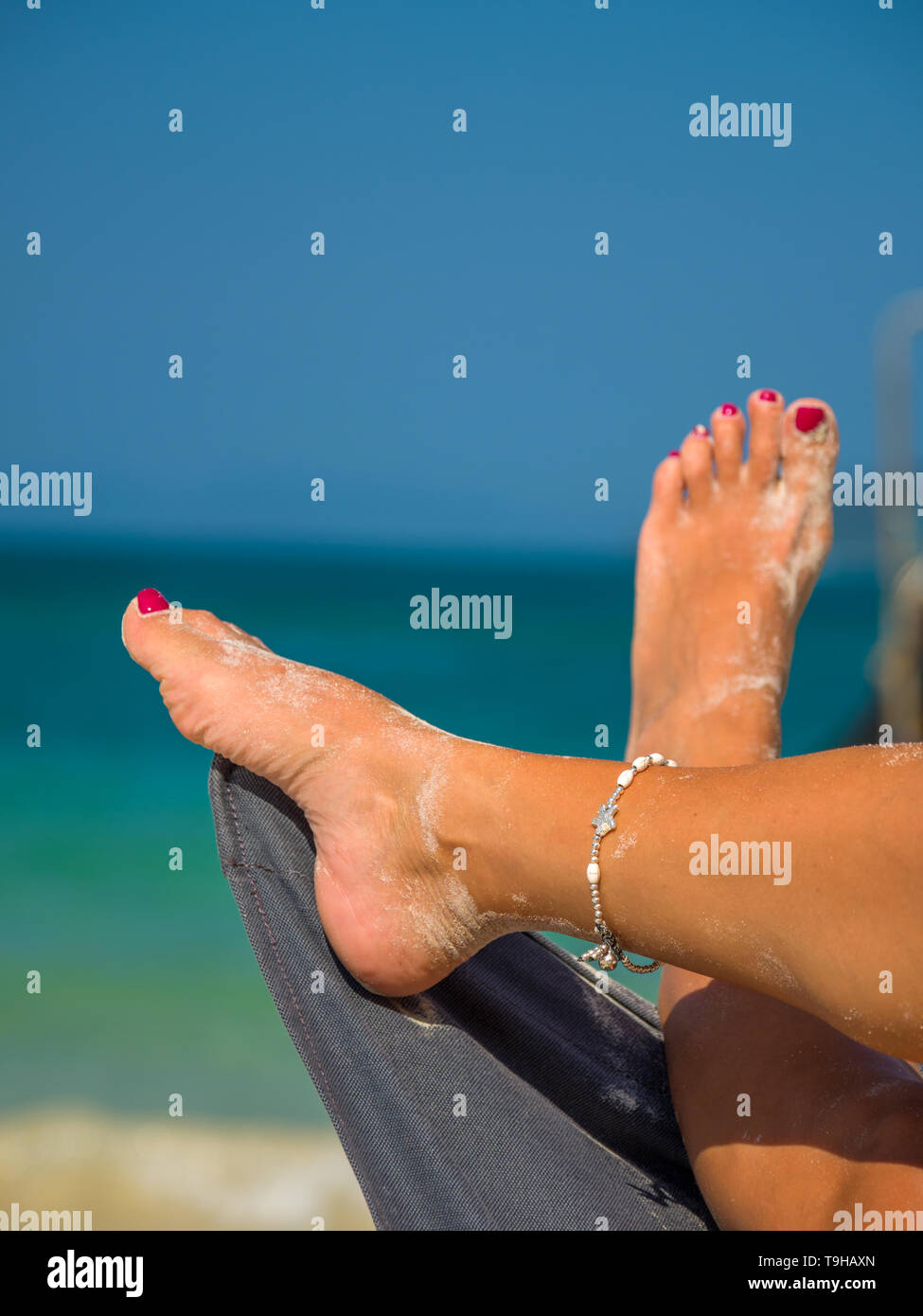 Legs of a woman at the beach - Stock Image