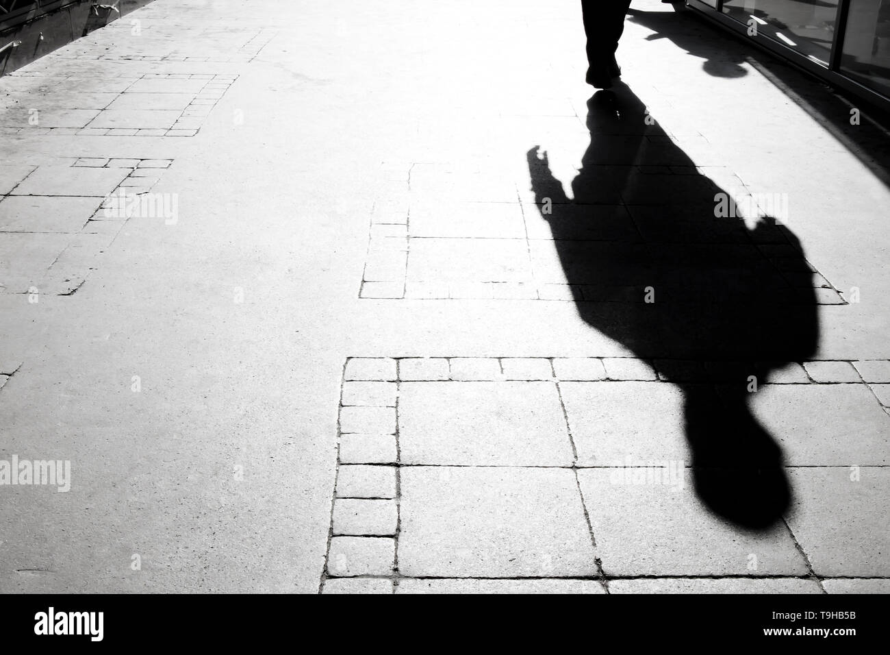 Blurry shadow silhouette of  a person  walking on city sidewalk - Stock Image