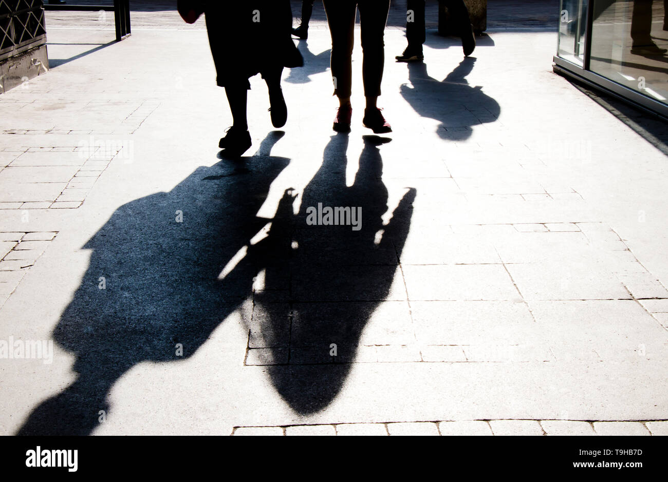 Blurry shadow silhouette of  people walking on city pedestrian street in high contrast black and white - Stock Image