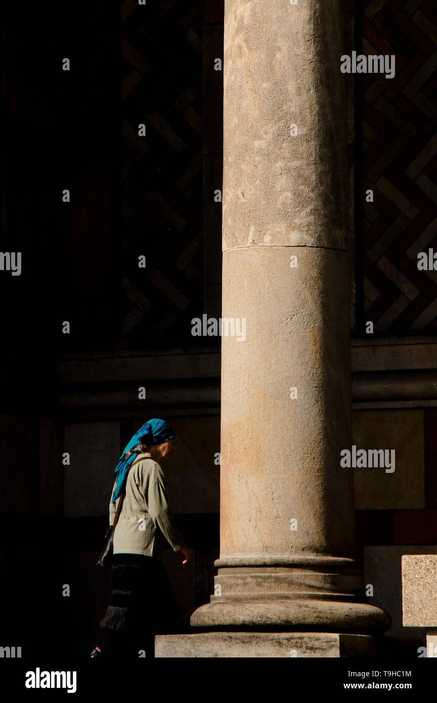 Belgrade, Serbia -  April 22, 2019: Senior woman wearing blue scarf walking in the arcade of Saint Mark's orthodox church - Stock Image