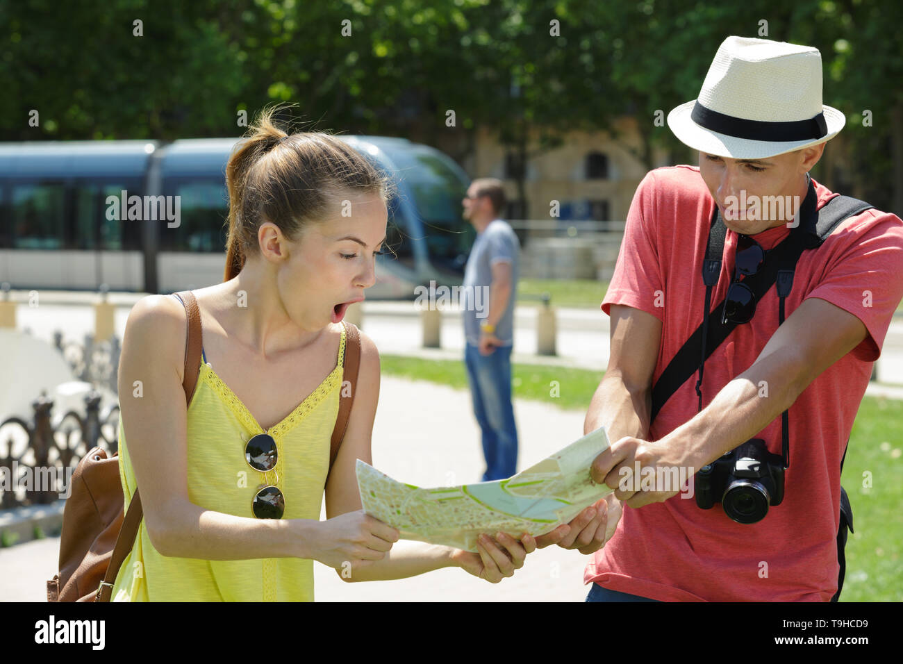young couple on holiday looking at map with shocked expressions - Stock Image