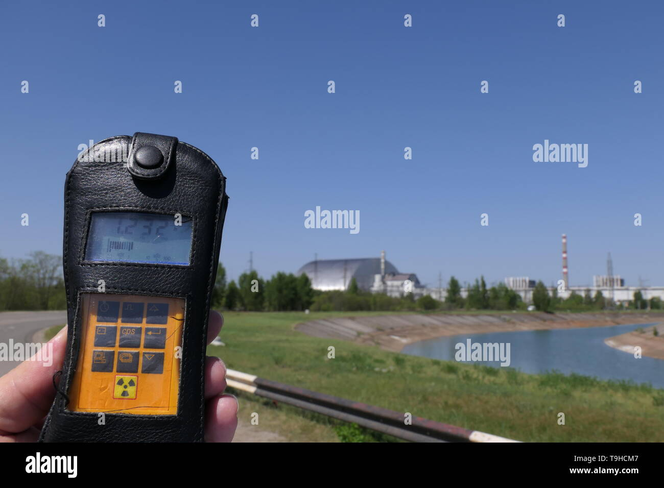 View of the Reactor 4 from a safe distance with a Geiger counter, inside the Chernobyl exclusion zone, Ukraine - Stock Image