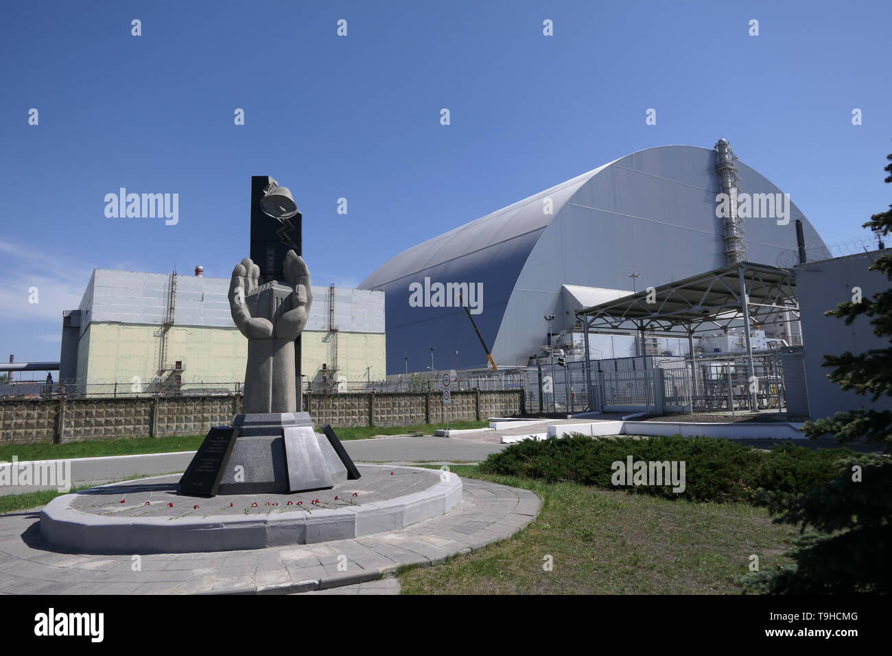 View of the destroyed Reactor 4 and the Memorial for the Chernobyl liquidators, Chernobyl exclusion zone, Ukraine - Stock Image