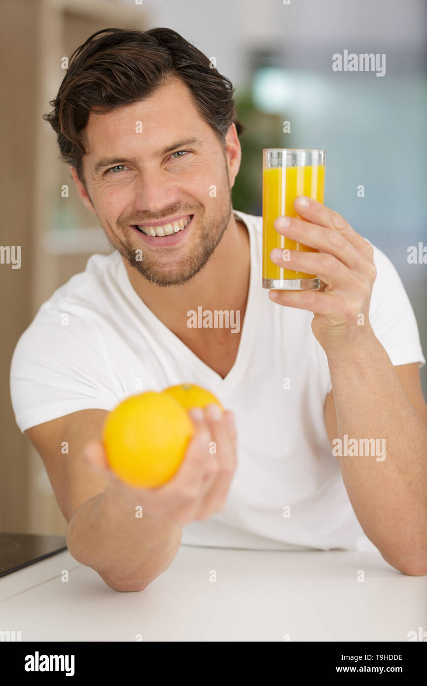 man holding orange juice and smiling in the kitchen - Stock Image