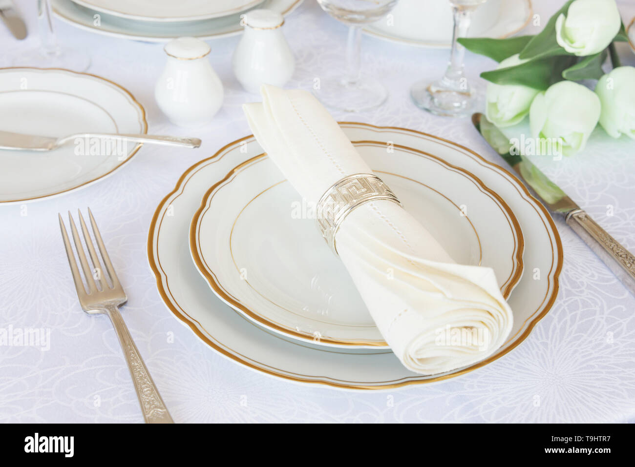 Classic serving for a gala dinner with luxurious porcelain, silverware and tulip flowers on a white tablecloth Stock Photo