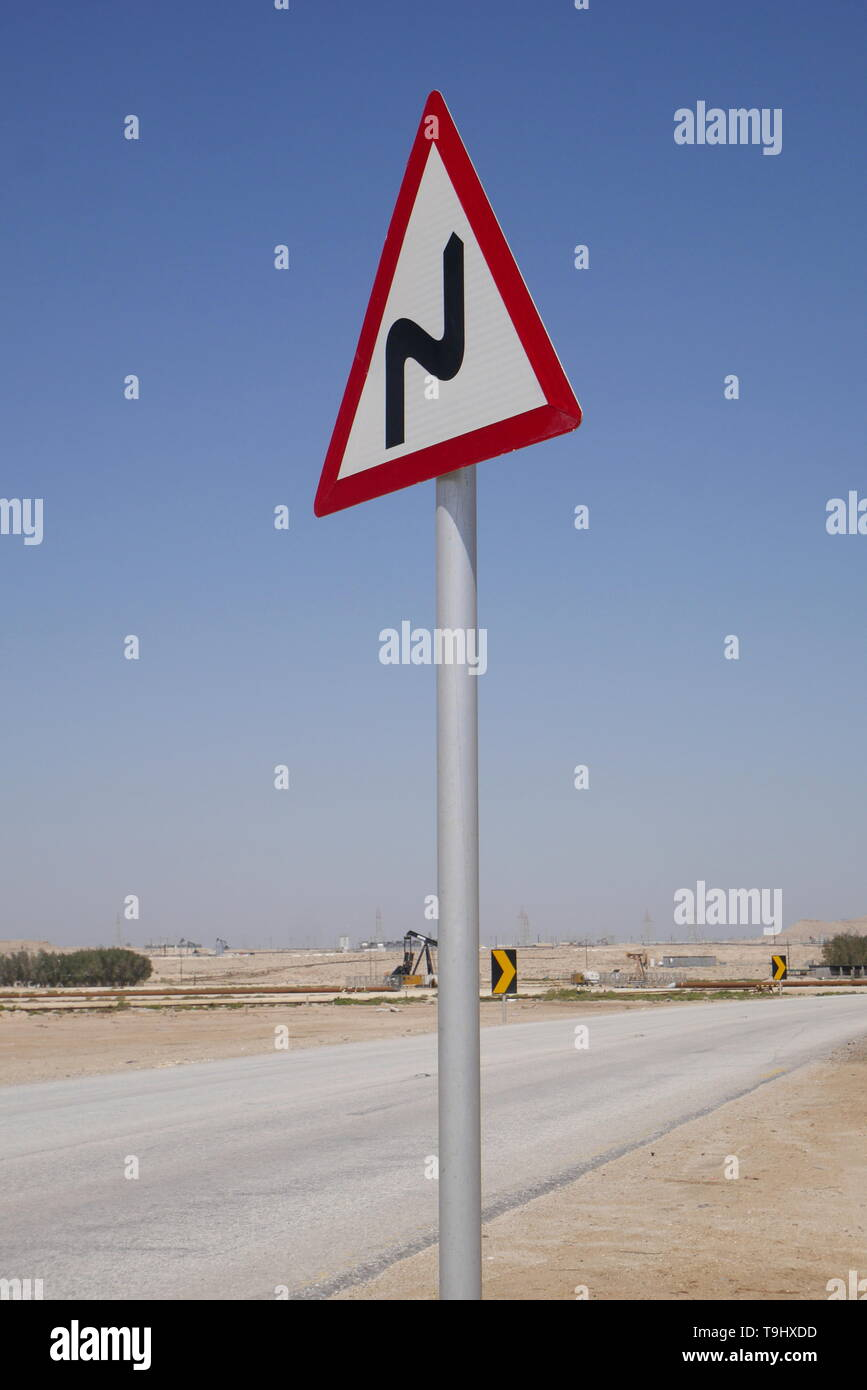 Road sign on a desert road showing bends ahead, Kingdom of Bahrain - Stock Image