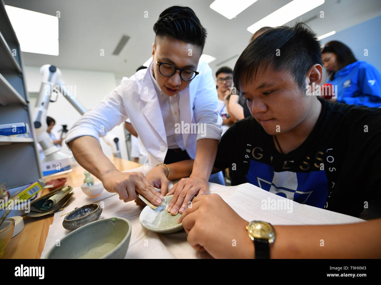 Hainan, China. 18th May, 2019. A restorer of ancient ceramics guides the audience to polish the ceramics at the China (Hainan) Museum of the South China Sea in Qionghai, south China, on May 18, 2019. The museum invited the audience to visit and experience the restoration of ancient ceramics on the International Museum Day. Credit: Guo Cheng/Xinhua/Alamy Live News Stock Photo