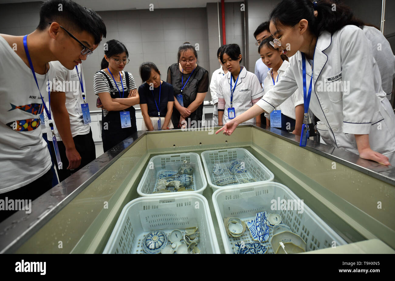 Hainan, China. 18th May, 2019. A restorer of ancient ceramics introduces the methods of desalting the ancient ceramics to the audience at the China (Hainan) Museum of the South China Sea in Qionghai, south China, on May 18, 2019. The museum invited the audience to visit and experience the restoration of ancient ceramics on the International Museum Day. Credit: Guo Cheng/Xinhua/Alamy Live News - Stock Image