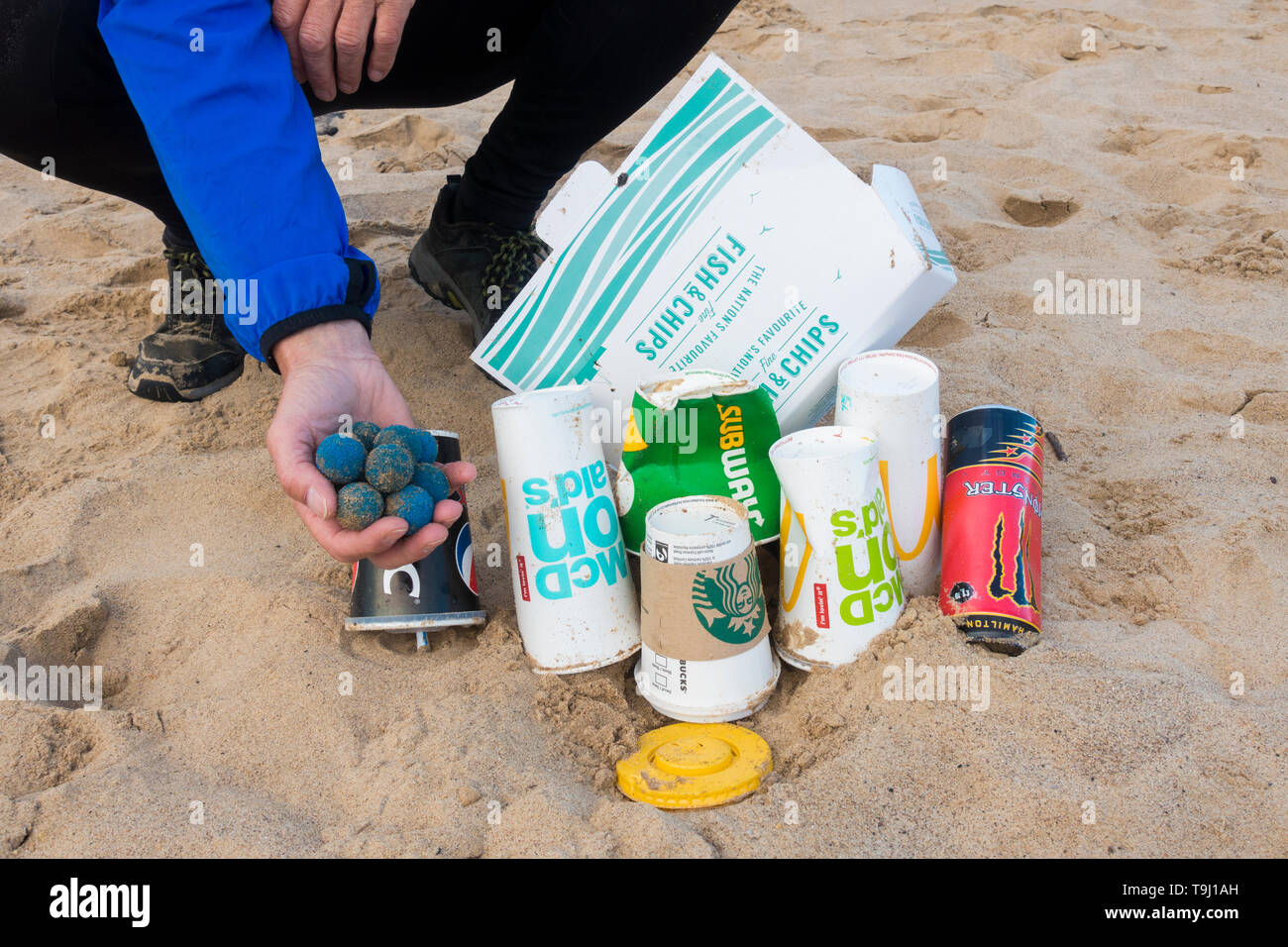 Seaton Carew, County Durham, UK. 19th May 2019. UK weather: a glorious morning for Plogging. A jogger collects rubbish on his morning run through the dunes at Seaton Carew on the north east coast of England. Plogging (picking up litter while jogging) is a Scandinavian lifestyle trend where joggers pick up rubbish/plastic as they run.Also found on the beach were Taprogge Balls (in jogger's hand), used to clean cooling pipes in power stations. Taprogge balls previously found on this stretch of coast were found to have come from the nearby Hartlepool nuclear power station (they are said to be har Stock Photo