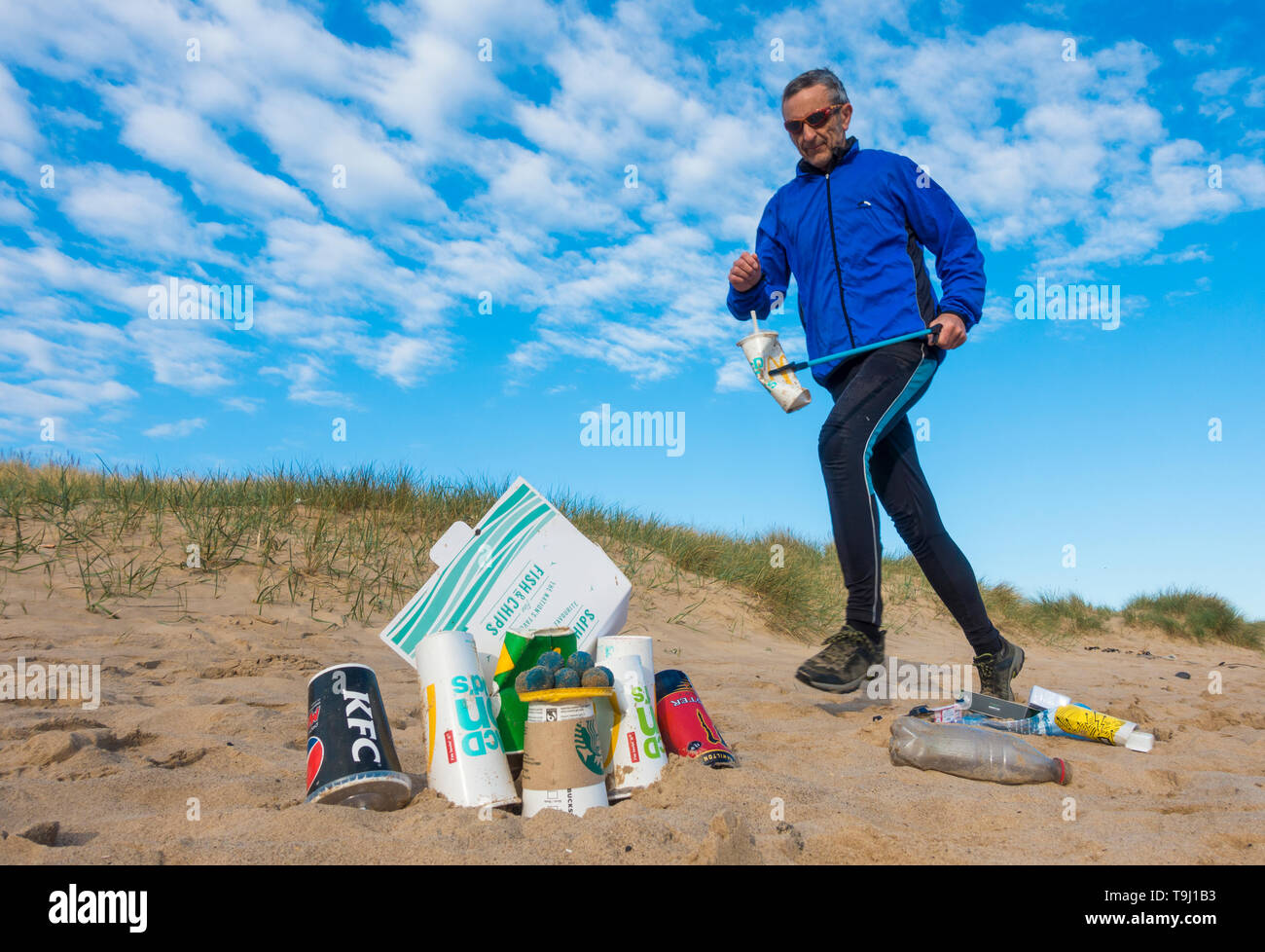 Seaton Carew, County Durham, UK. 19th May 2019. UK weather: a glorious morning for Plogging. A jogger collects rubbish on his morning run through the dunes at Seaton Carew on the north east coast of England. Plogging (picking up litter while jogging) is a Scandinavian lifestyle trend where joggers pick up rubbish/plastic as they run. Credit: Alan Dawson/Alamy Live News Stock Photo