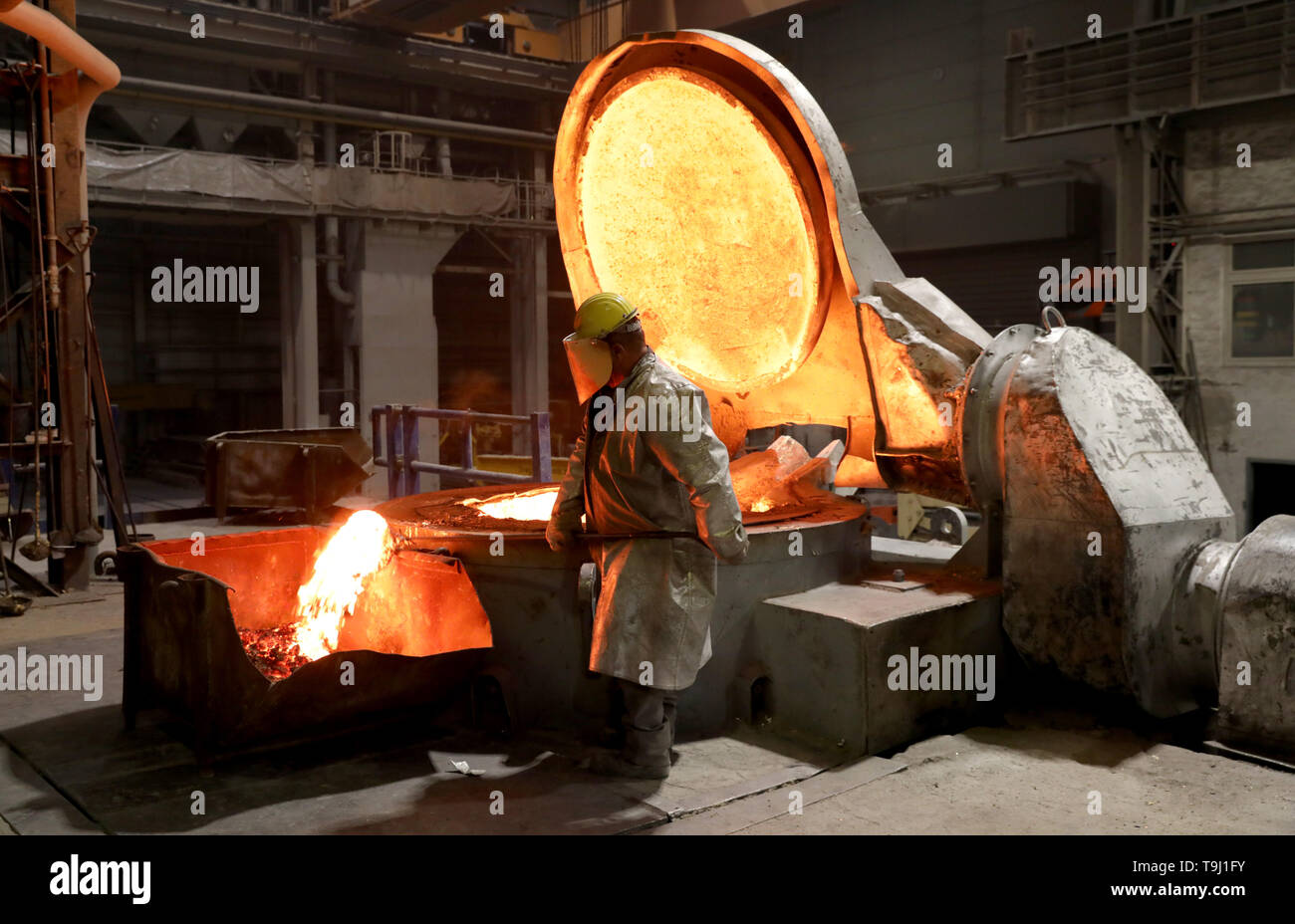 Waren, Germany. 08th May, 2019. In the foundry of Mecklenburger Metallguss GmbH MMG the slag is removed from the aluminium bronze before casting a large ship propeller. A total of 165 tons of material with a temperature of about 1,170 degrees is poured into a mold. The propeller for a large Korean container freighter will later have a diameter of 10.40 meters and weigh 117 tons. Less than a year after its transition to independence, MMG sees itself on the upswing again. Credit: Bernd Wüstneck/dpa/Alamy Live News - Stock Image