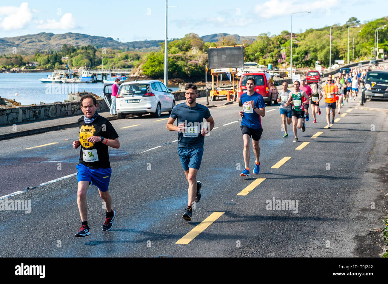 Glengarriff, West Cork, Ireland. 19th May, 2019. The pack races from Glengarriff just agfter the start of the annual Bay Run.  The race, which is a half marathon, runs from Glengarriff to Bantry. Credit: Andy Gibson/Alamy Live News. - Stock Image