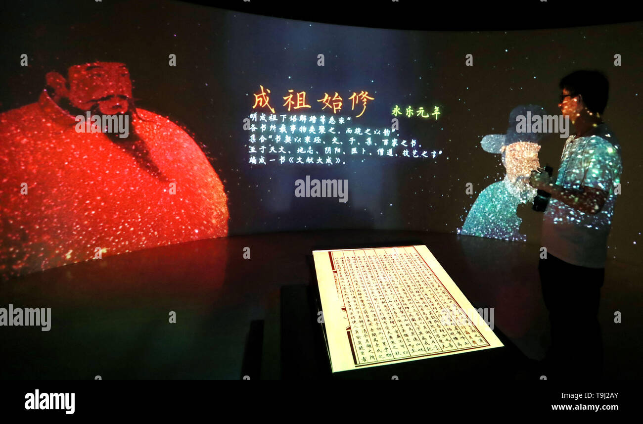 Beijing, China. 18th May, 2019. A visitor watches introduction of Yongle Encyclopaedia at National Library of China in Beijing, capital of China, May 18, 2019. Yongle Encyclopaedia is China's first encyclopaedia compiled in the Ming Dynasty (1368-1644). China is holding a rich variety of exhibitions and activities on the culture of Asian countries and regions as well as exchanges among them. Credit: Pan Xu/Xinhua/Alamy Live News - Stock Image