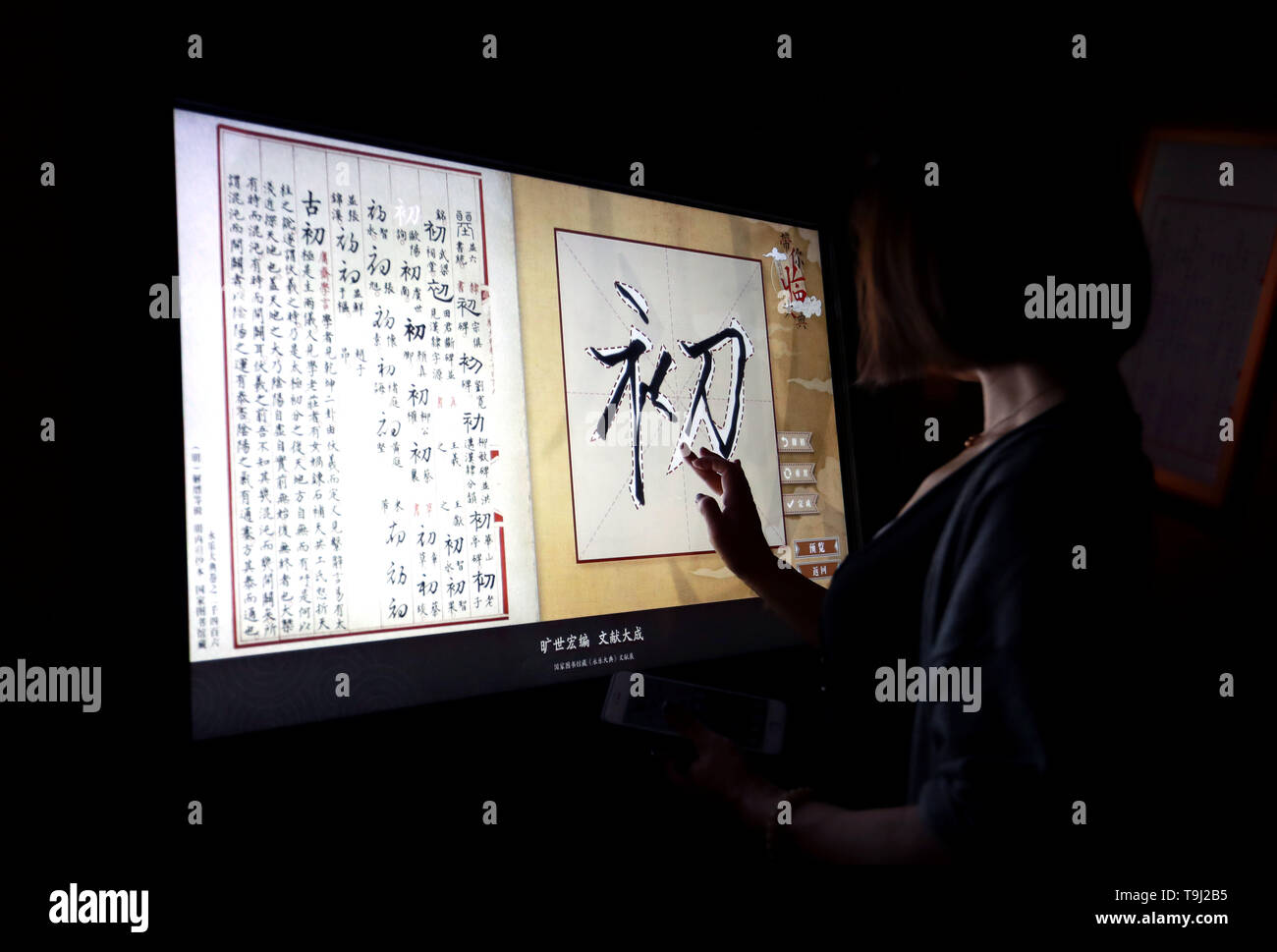 Beijing, China. 18th May, 2019. A visitor copies characters at an exhibition on Yongle Encyclopaedia at National Library of China in Beijing, capital of China, May 18, 2019. Yongle Encyclopaedia is China's first encyclopaedia compiled in the Ming Dynasty (1368-1644). China is holding a rich variety of exhibitions and activities on the culture of Asian countries and regions as well as exchanges among them. Credit: Pan Xu/Xinhua/Alamy Live News - Stock Image