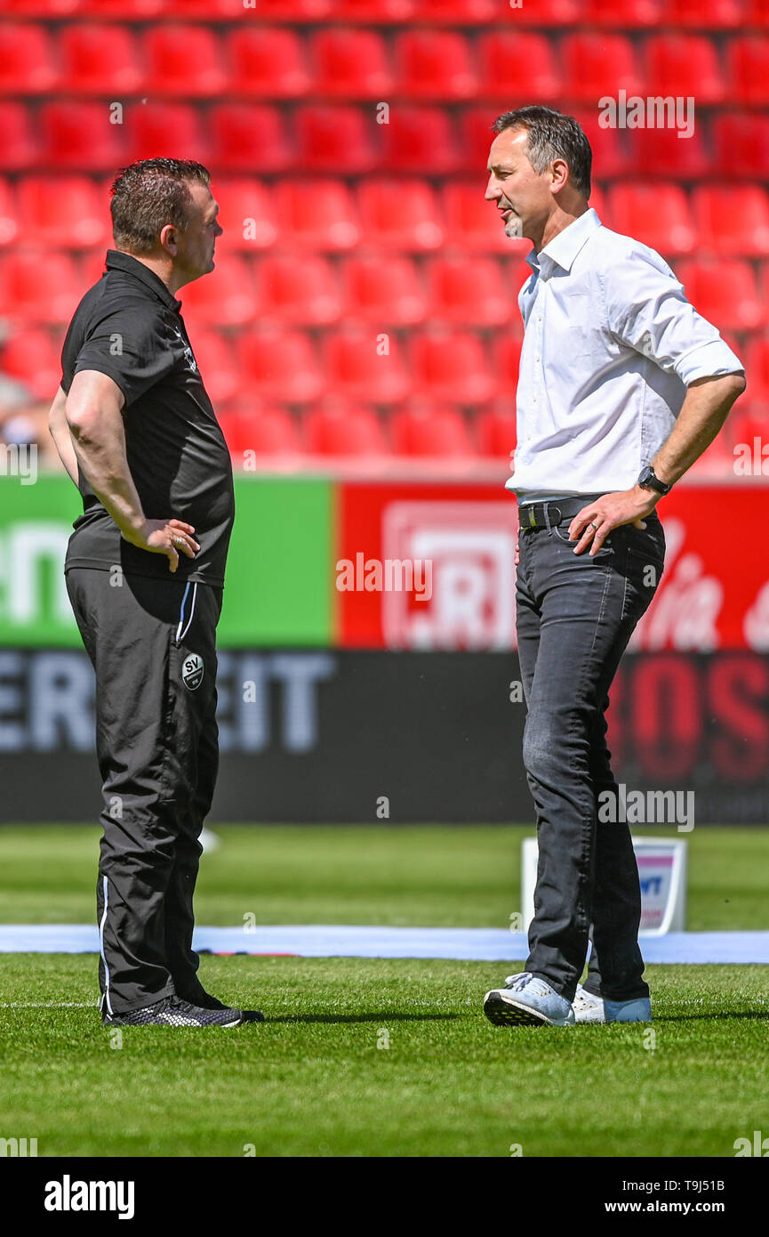 Regensburg, Germany. 19th May, 2019. Soccer: 2nd Bundesliga, Jahn Regensburg - SV Sandhausen, 34th matchday in the Continental Arena. Coach Uwe Koschinat from Sandhausen (l) talks to coach Achim Beierlorzer from Regensburg before the match. Credit: Armin Weigel/dpa - IMPORTANT NOTE: In accordance with the requirements of the DFL Deutsche Fußball Liga or the DFB Deutscher Fußball-Bund, it is prohibited to use or have used photographs taken in the stadium and/or the match in the form of sequence images and/or video-like photo sequences./dpa/Alamy Live News - Stock Image