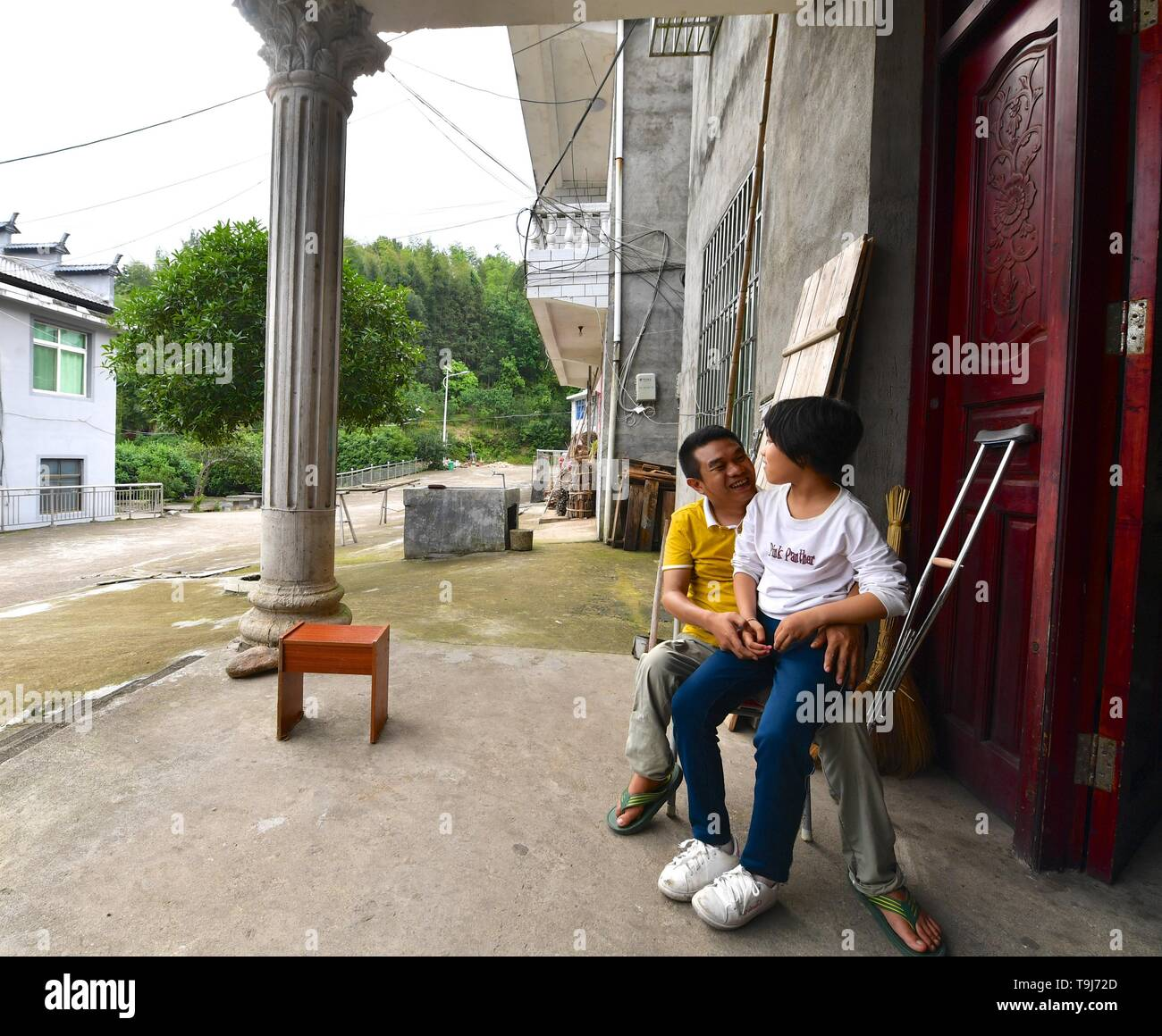 (190519) -- NANCHANG, May 19, 2019 (Xinhua) -- Lin Fusheng (L) chats with his daughter in front of their home in Lichuan County, east China's Jiangxi Province, May 16, 2019. Lin Fusheng, a villager from Hualian Village of Huashan Township in Lichuan County, suffered from physical disability because of infantile paralysis. Despite that, Lin stuck with his dream of becoming a painter.      As Lichuan County witnessed rapid development of oil painting industry in 2013, Lin returned to his hometown and grew as a professional painter with the help of local government. Now Lin owns a studio at an oi - Stock Image