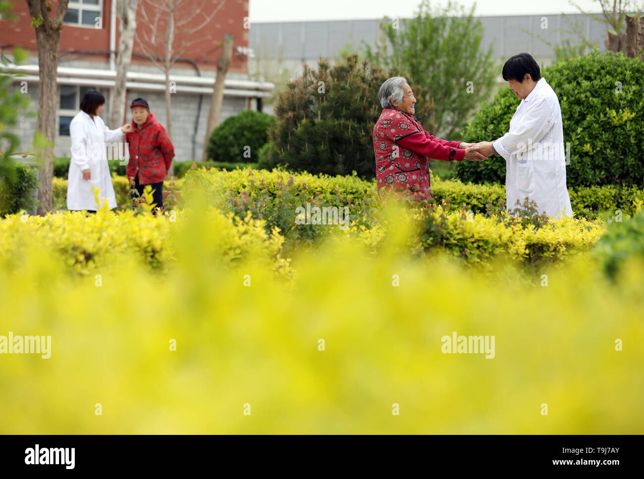 Beijing, China's Hebei Province. 5th May, 2019. Elderly citizens are accompanied by medical care personnels at an elderly care center in Taocheng District of Hengshui City, north China's Hebei Province, May 5, 2019. Chinese economy is transitioning from high-speed growth to high-quality development. Credit: Mu Yu/Xinhua/Alamy Live News - Stock Image