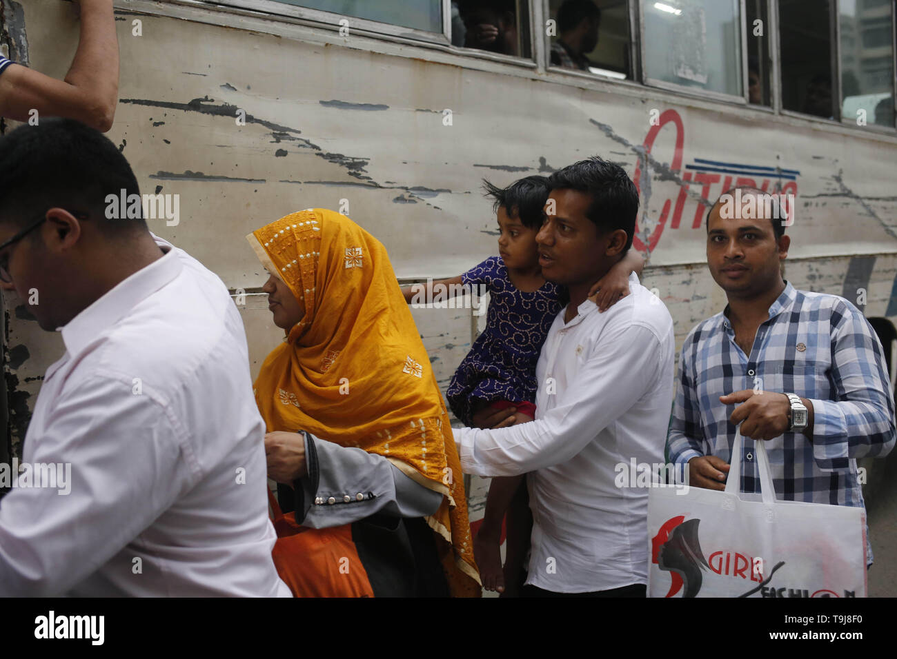 May 19, 2019 - Dhaka, Bangladesh - A family with a child try to get on a public transport in a rush hour during Ramadan in Dhaka. Passenger transport service is very incomprehensible for women in the capital. (Credit Image: © MD Mehedi Hasan/ZUMA Wire) Stock Photo