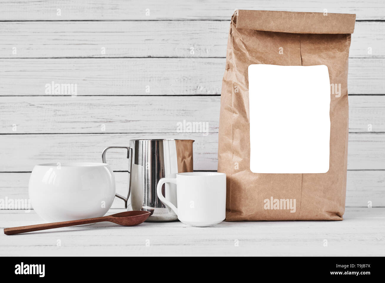 Coffee cup, craft paper bag and stainless pitcher on white background, copy space - Stock Image