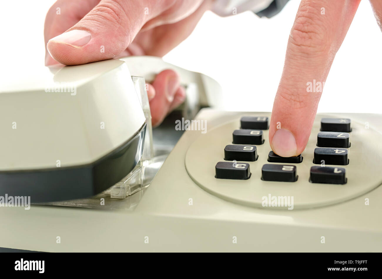 Detail of dialing a number on and old telephone. Isolated over white background. - Stock Image