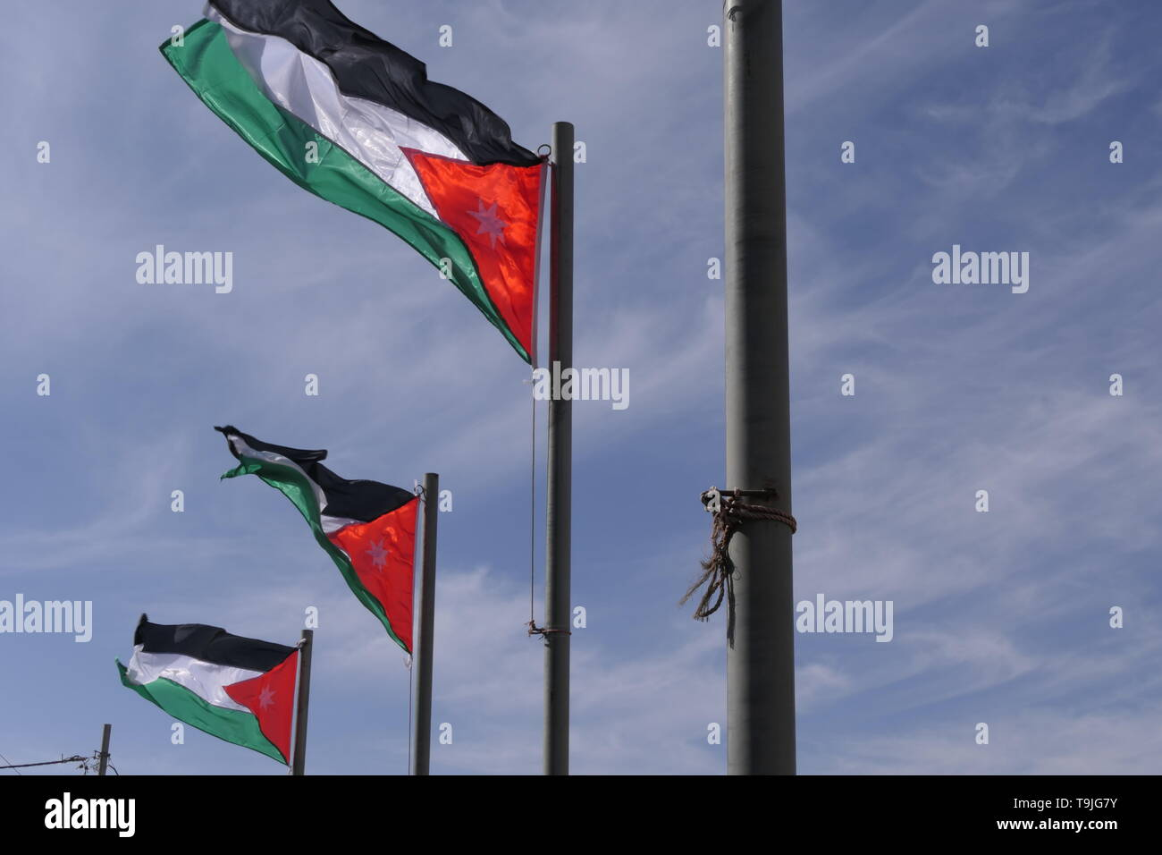 National flag of Jordan on a flagpole in the Hashemite Kingdom of Jordan - Stock Image